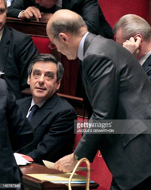 French Prime Minister Francois Fillon speaks with France's Foreign Affairs minister Alain Juppe on March 6 2012 at the National Assembly on the last...