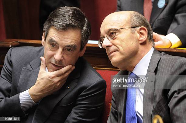 French Prime Minister Francois Fillon speaks with French Foreign Affairs Minister Alain Juppe during a debate with French MP's focused on air strikes...