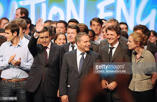 French Prime minister Francois Fillon waves next to UMP French right wing party General Secretary Xavier Bertrand Industry minister Christian Estrosi...