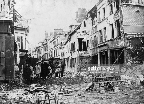 French Prime Minister Georges Clemenceau picks his way through the rubble of a French town towards the end of World War I 1918 A sign at the end of...