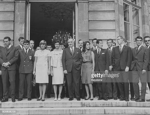 French Prime Minister Georges Pompidou posing for a portrait with a group of French Olympic medal winners Joseph Gonzales Christine Caron Maryvonne...