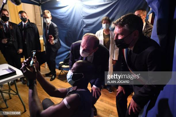 French Prime Minister Jean Castex and Seine-Saint-Denis member of Parliament Stephane Teste pose for a selfie with a man who has just received a dose...