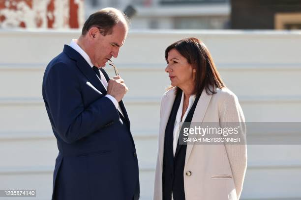 French Prime Minister Jean Castex chats with Paris' Socialist Party Mayor Anne Hidalgo upon their arrival at a building site of the Olympic Village...