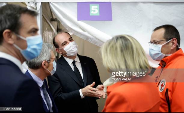 French Prime Minister Jean Castex flanked by Health Minister Olivier Veran speak to French Red Cross workers as they visit a Covid-19 vaccination...