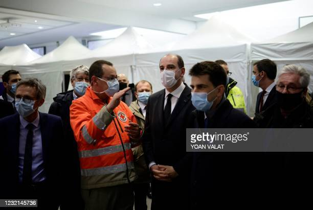 French Prime Minister Jean Castex speaks with a French Red Cross worker during a visit of the Covid-19 vaccination center setup inside the Stade de...
