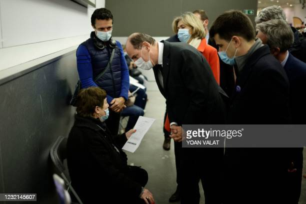 French Prime Minister Jean Castex speaks with a woman queueing as he visits the Covid-19 vaccination center setup inside the Stade de France stadium...