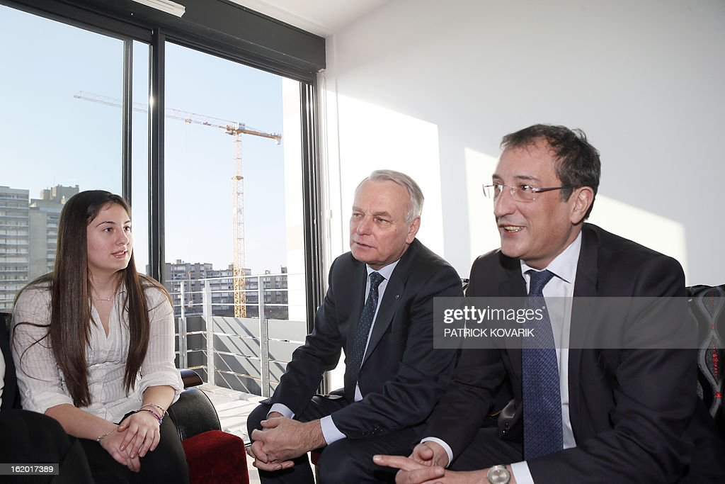 French Prime Minister Jean-Marc Ayrault (C) and French Junior Minister for Cities Francois Lamy (R) are seated beside a resident in her apartment during a visit to a residential building in Clichy-sous-Bois, northern suburb of Paris on February 18, 2013, as part of the French government's urban policy.
