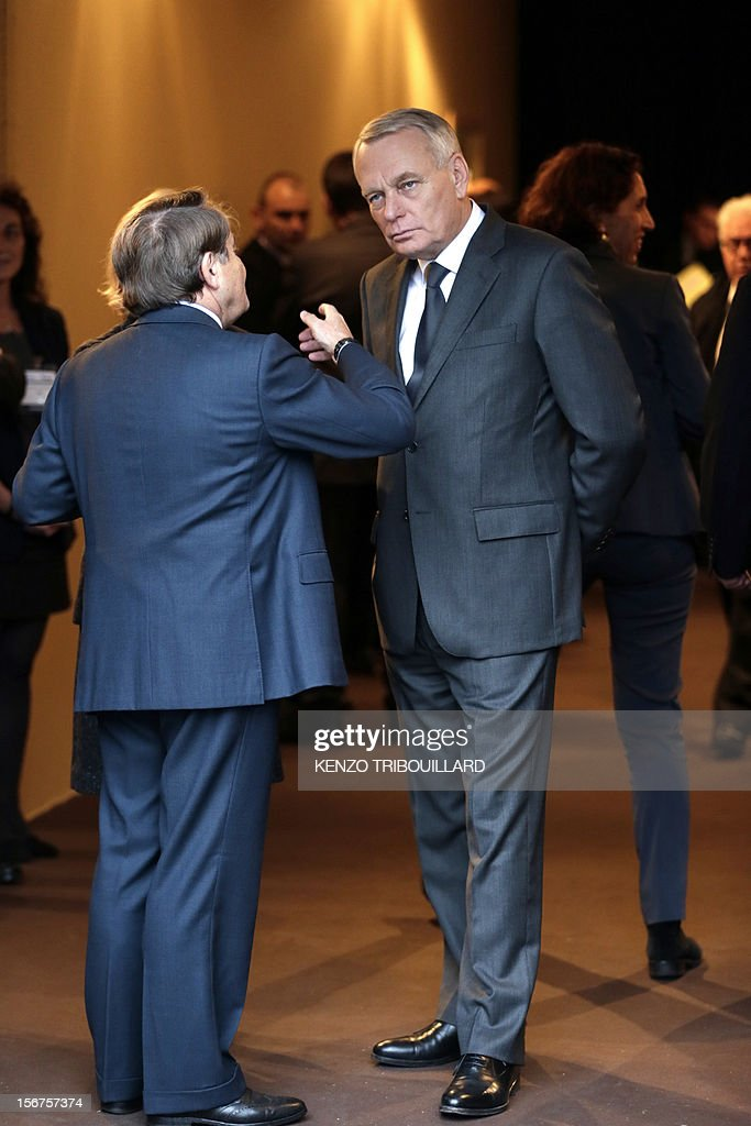 French Prime Minister Jean-Marc Ayrault (R) listens to Andre Laignel, General Secretary of the French Mayors Committee (AMF) as he arrives for the opening ceremony of the 95th French Mayors congress, on November 20, 2012 in Paris.