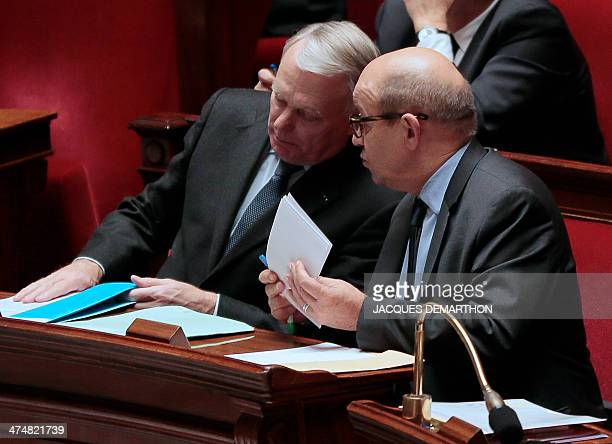 French Prime Minister JeanMarc Ayrault listens to French Defence Minister JeanYves Le Drian after delivering a speech in the National Assembly in...