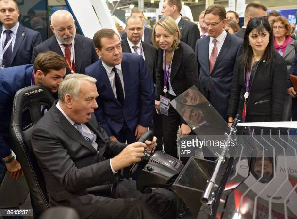 French Prime Minister JeanMarc Ayrault reacts as he drives a simulator beside Russian Prime Minister Dmitry Medvedev and their Finnish counterpart...