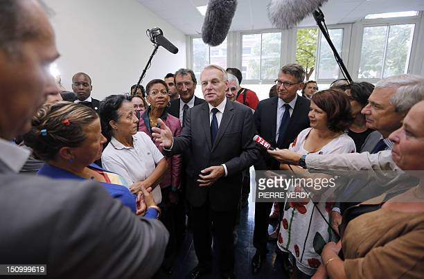 French Prime Minister JeanMarc Ayrault speaks with professors and parents as French Junior Minister for Educational Success George PauLangevin French...
