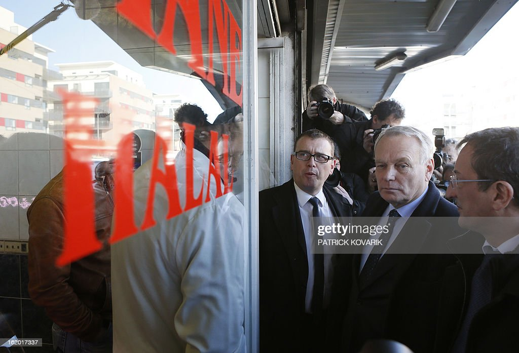 French Prime Minister Jean-Marc Ayrault (2ndR), surrounded by the mayor of Clichy-sous-Bois Olivier Klein (C) and French Junior Minister for Cities Francois Lamy (R) stands outside a Halal butcher shop during a visit to Clichy-sous-Bois, northern suburb of Paris on February 18, 2013, as part of the French government's urban policy.