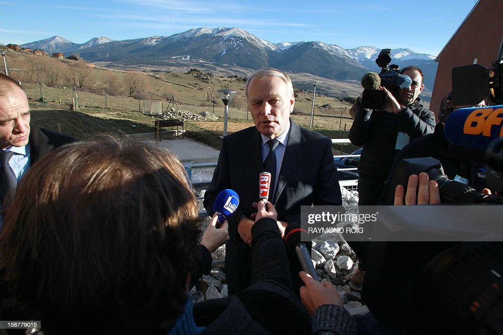 French Prime minister Jean-Marc Ayrault (C) talks to journalists during a visit at the Font-Romeu gendarmes headquarters, southern France, on December 28, 2012. AFP PHOTO / RAYMOND