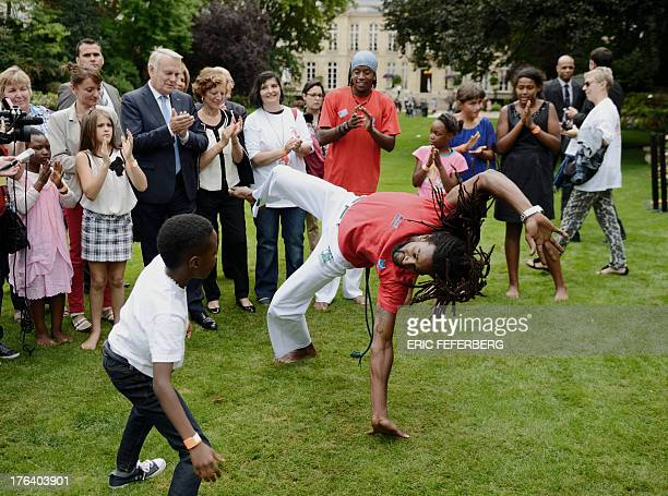 French Prime Minister JeanMarc Ayrault watches a capoeira demonstration during a picnic party with children who cannot afford to go on holidays in...