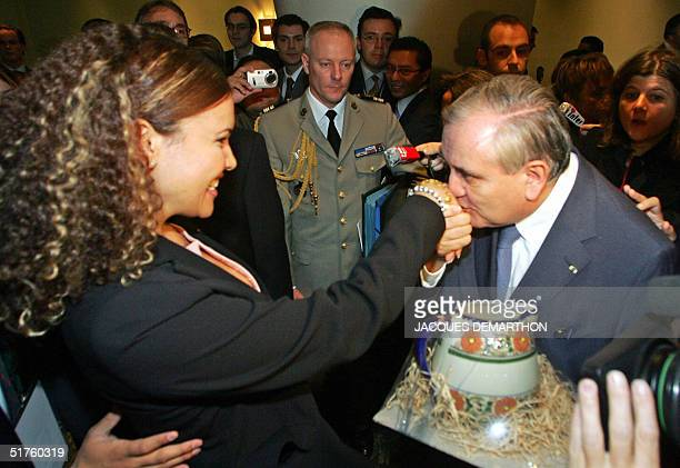 French Prime Minister JeanPierre Raffarin kisses the hand of a young business woman after receiving a gift 18 November 2004 in Mexico during a...