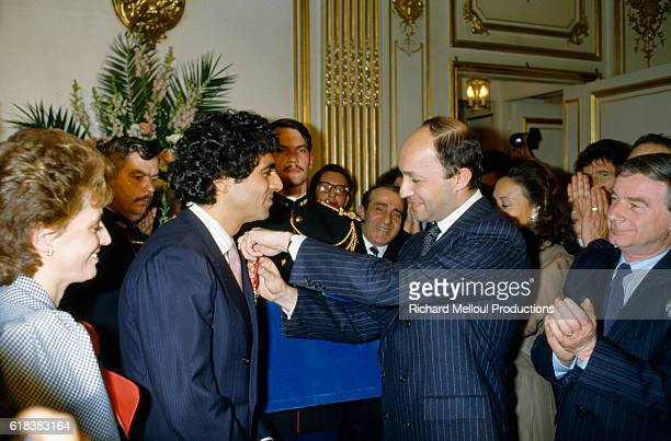 French Prime Minister Laurent Fabius presents French-Algerian singer Enrico Macias with the Legion of Honor medal.