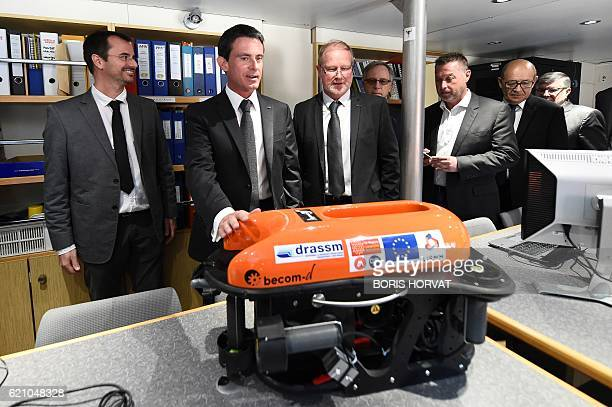 French Prime minister Manuel Valls and director of the French Marine and Submarine Archeological Department Michel L'Hour look at a remotely operated...