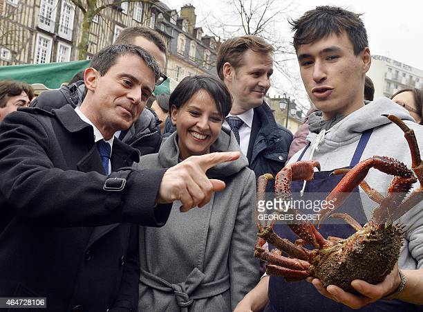 French Prime Minister Manuel Valls and French Education Minister Najat VallaudBelkacem talk with a sea products seller holding a spider crab while...