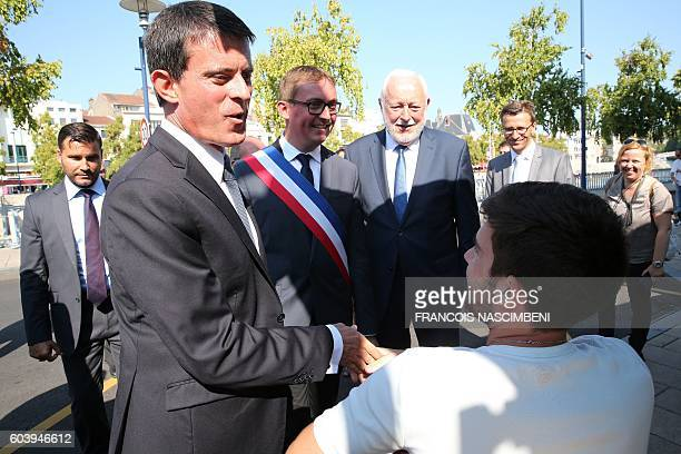 French Prime Minister Manuel Valls and Verdun socialist mayor Samuel Hazard meet with a resident within a ceremony in Verdun northeastern France on...