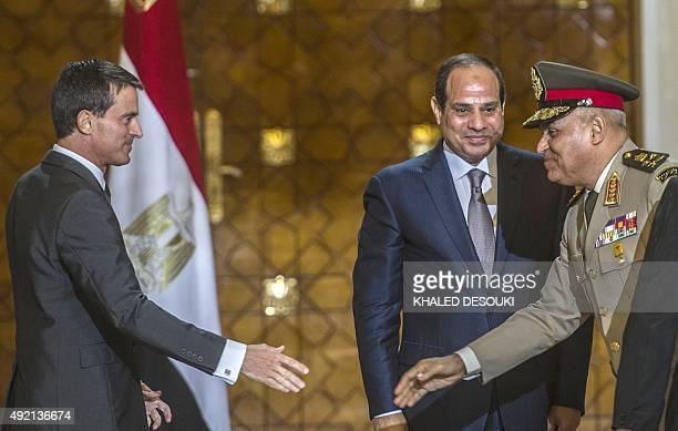 French Prime Minister Manuel Valls arrives to shake hands with Egyptian Defence minister General Sedki Sobhi as Egyptian President Abdel Fattah...