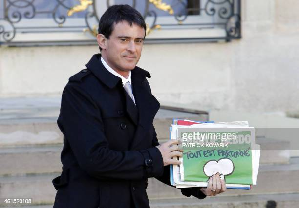 French Prime Minister Manuel Valls holding the latest edition of French satirical magazine Charlie Hebdo leaves the Elysee Palace after a weekly...
