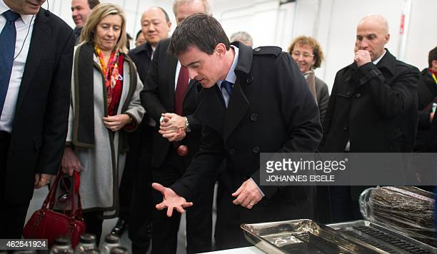 French Prime Minister Manuel Valls plays with gum sample as he visits the Michelin Tyre Research and Development Center in Shanghai on January 31...