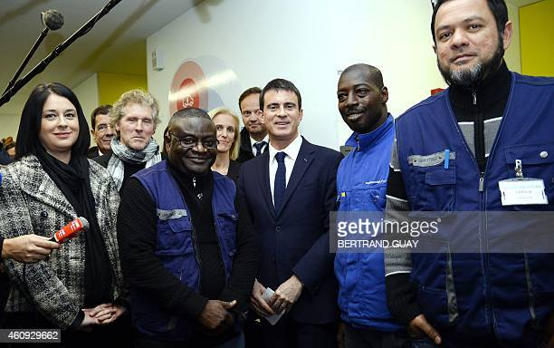 French Prime Minister Manuel Valls poses on December 31, 2014 with a staff during a visit to a center caring for the homeless in Montrouge, a...