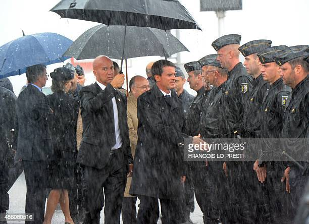 French Prime minister Manuel Valls shakes hands with policemen as he arrives to visit the Eurotunnel terminal in the northern French port of Calais...