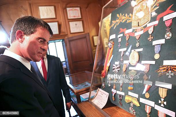 French Prime Minister Manuel Valls views medals at the War Medals museum of the Verdun city hall within a ceremony in Verdun northeastern France on...