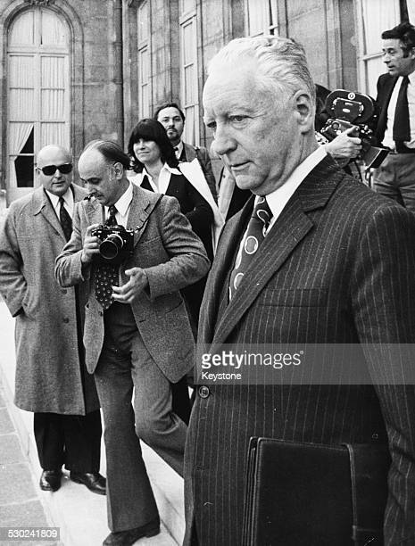 French Prime Minister Pierre Messmer photographed by the press as he leaves a cabinet meeting at the Palais de l'Elysee France circa 1973