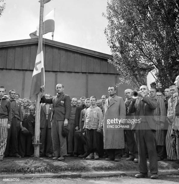 French prisoners raise the flag of Free France with the Lorraine cross while singing the national anthem 'La Marseillaise' 29 April 1945 upon the...