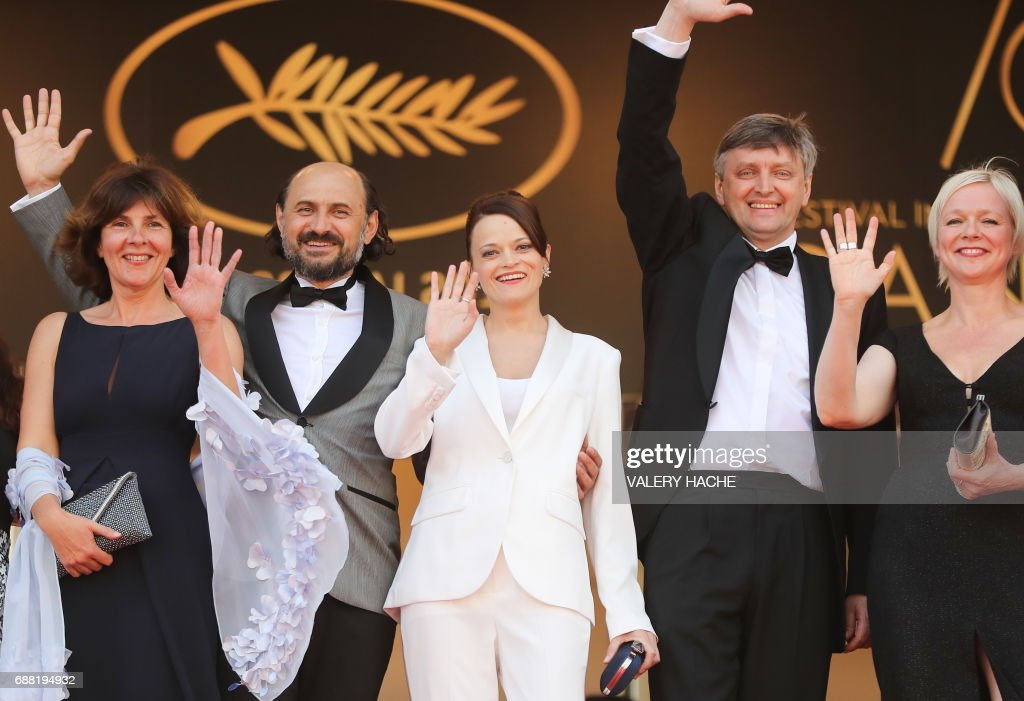French producer Carine Leblanc, Moldovan actor Valeriu Andriuta, actress Vasilina Makovtseva, Russian director Sergei Loznitsa and Danish producer Marianne Slot wave as they arrive on May 25, 2017 for the screening of the film 'Krotkaya' (A Gentle Creature) at the 70th edition of the Cannes Film Festival in Cannes, southern France. / AFP PHOTO / Valery HACHE