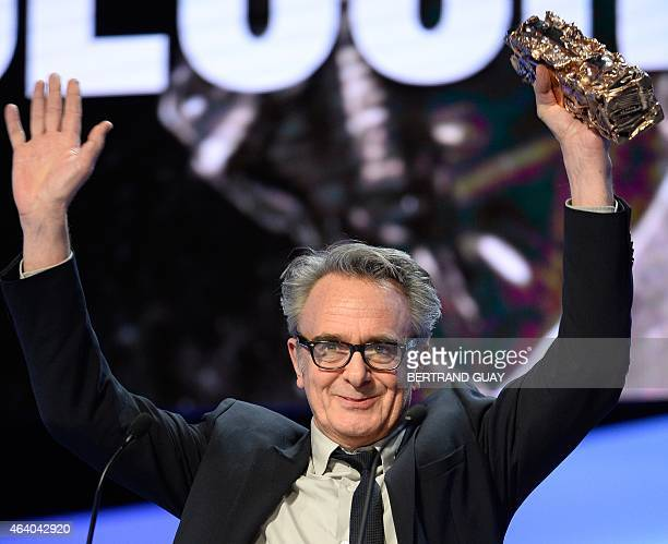 French production designer Thierry Flamand raises his trophy on stage after winning the Best Set Design award for La Belle et la Bete during the 40th...