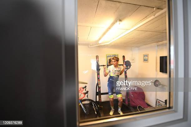 French professional cyclist Yoann Offredo of WantyGobert Cycling Team lifts weights as he trains in the garage of his house converted into a sports...