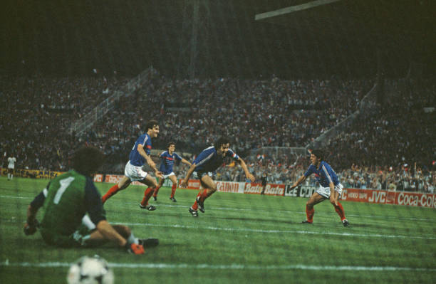 French professional footballer Michel Platini throws his arms out wide after scoring the winning goal for the France national team after 119 minutes...