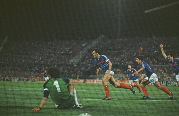French professional footballer Michel Platini turns away from goal followed by teammate Alain Giresse after scoring the winning goal for the France...