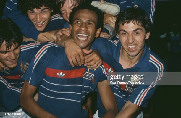 French professional footballers Jean Tigana and Alain Giresse celebrate with their teammates after France beat Spain 2-0 in the final of the UEFA...
