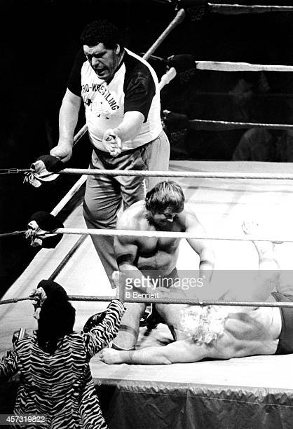 French professional wrestler and actor Andre the Giant in the ring as a special guest referee looks on as Rowdy Roddy Piper grabs Adrian Adonis by...