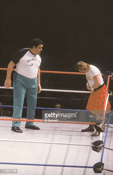 French professional wrestler and actor Andre the Giant in the ring as a special guest referee looks on as Rowdy Roddy Piper adjusts his kilt before...
