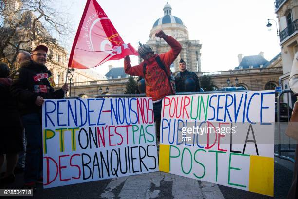 French protester JeanBaptiste Redde aka Voltuan stands beside a gendarme as he joins employees of French Postal service 'La Poste' gathering outside...