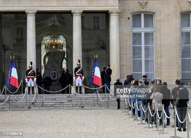 TOPSHOT French public queue to pay tribute in front of a picture of the late French President Jacques Chirac displayed at the Elysee presidential...