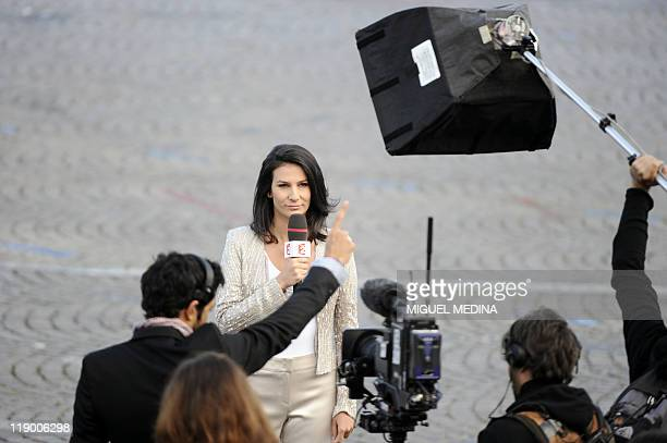 French public TV channel France 2 host Marie Drucker holds her microphone before a live report during the annual Bastille day parade on the...