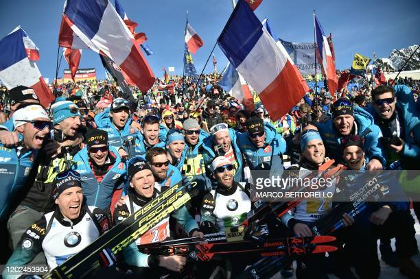 French Quentin Fillon Maillet, French Emilien Jacquelin, French Martin Fourcade and French Simon Desthieux celebrate with their team staff and fans...