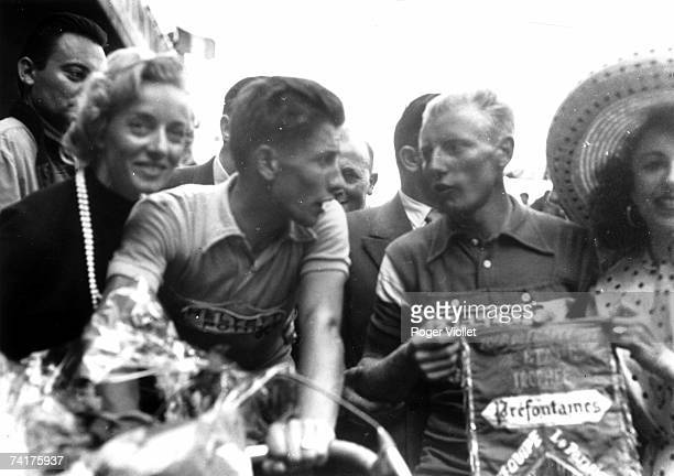 French racing cyclist Jacques Anquetil winner of the 1957 Tour de France celebrating his victory with wife Janine fellow cyclist Andre Darrigade and...