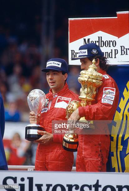 French racing driver Alain Prost pictured on right on the podium with the trophy after driving the Marlboro McLaren International McLaren MP4/2B...