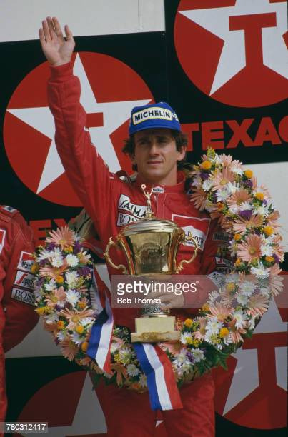 French racing driver Alain Prost waves to crowds of supporters from the podium after driving the Marlboro McLaren International McLaren MP4/2B...