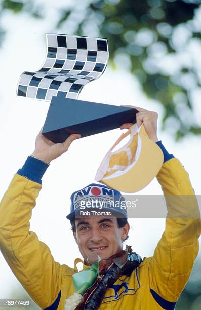 French racing driver Jean Alesi holds the trophy in the air after driving the Eddie Jordan racing Reynard 89D Mugen Honda to finish in first place to...