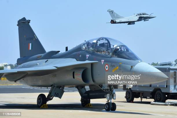 A French Rafale fighter flies over an Indian Airforce Tejas Aircraft with Bipin Rawat the 27th Chief of Army Staff of the Indian Army on board in the...