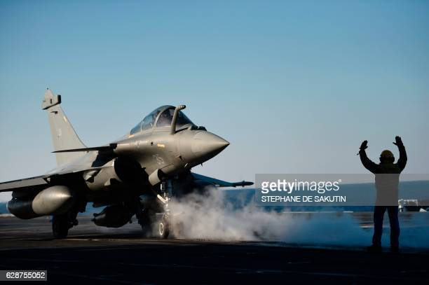 A French Rafale fighter jet takes off from the deck of France's aircraft carrier CharlesdeGaulle operating in the eastern Mediterranean Sea on...