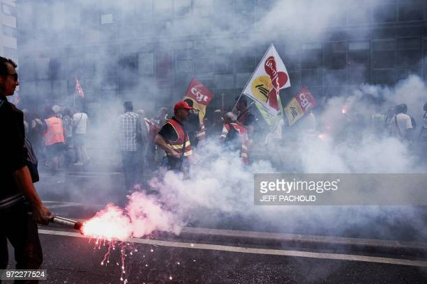 French railway workers demonstrate with banners, flags and flares in Lyon, east-central France, on June 12 on the 15th day of rolling train strikes...